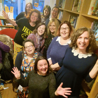 A group of white women are smiling up at the camera and making happy jazz-hands. They are in a bookshop.
