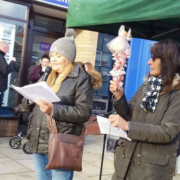 A white woman with long blonde hair wearing a grey bobble hat is reading poetry from a book at an outdoors festival stall. Another white woman with shorter dark brown hair is with her, holding a toy fairy on a decorated stick.