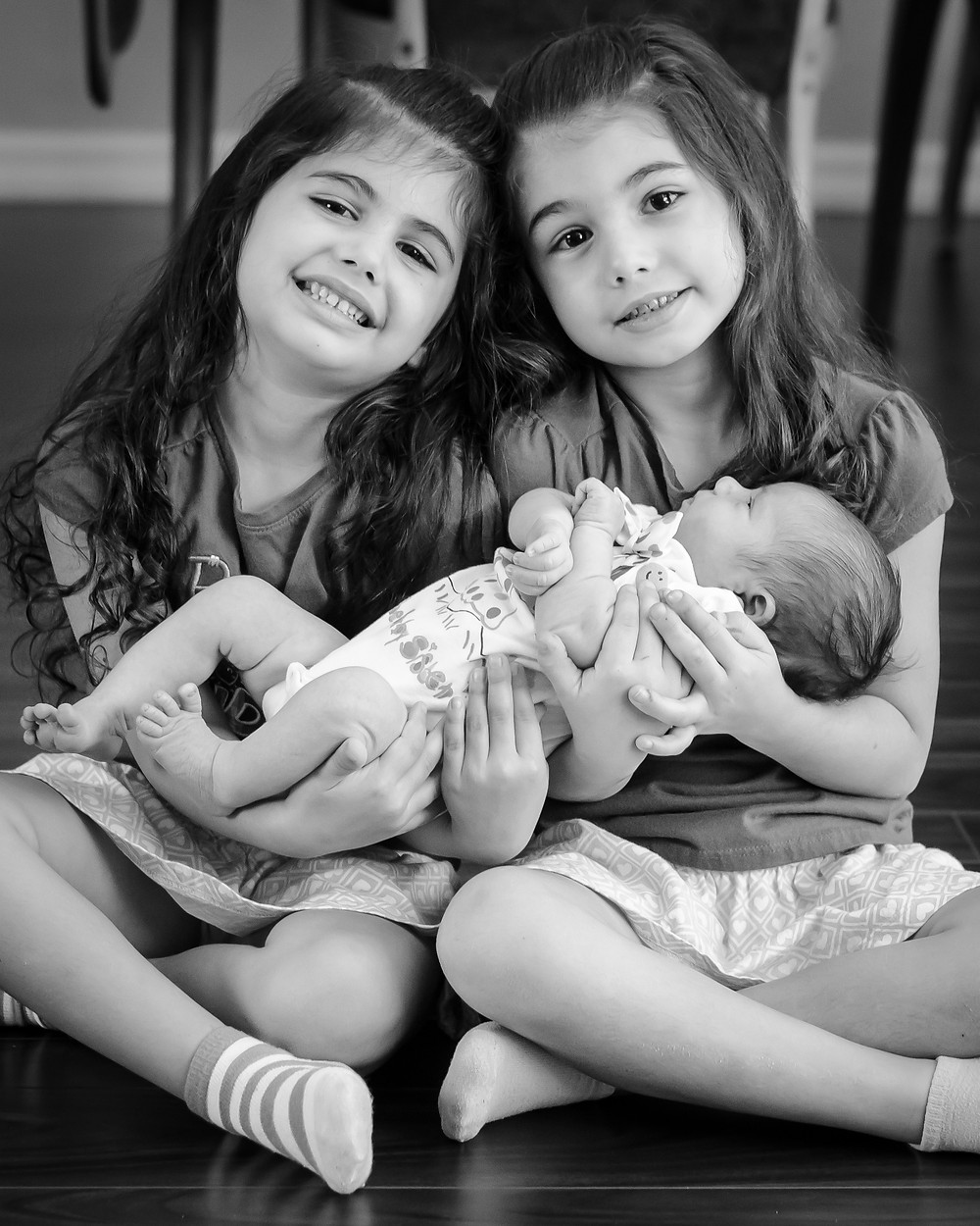 The girls hold sweet Beatrice in the living room.