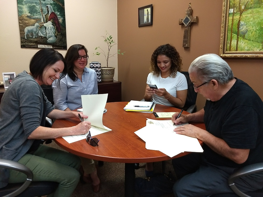 KTHA Executive Director Machael Smith and Deacon Henry Medina sign partnership agreement between Homeless Alliance and Bethlehem Center.