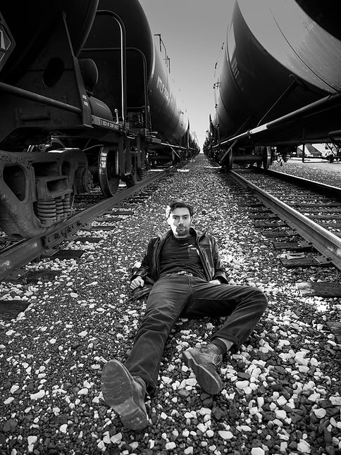 Actor Michael Massaad laying down inbetween two trains