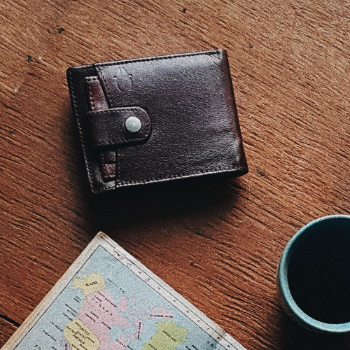 Photo of wallet next to map. A person planning a vacation.