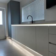 Ultra modern handleless kitchen with white quartz worktops and LED lighting