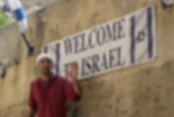 Joel Meyer Israel Tours Workshops Tourguide wearing a galabiya guiding a group in Jaffa, Israel in front of an Israeli Flag Sign