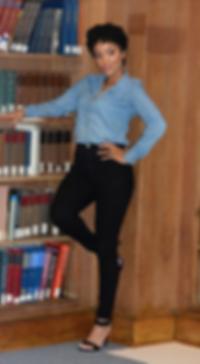 Toni R. Settles in front of bookshelf