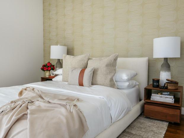 white-upholstered-bed-teak-nightstands-swirly-wallpaper-guest-bedroom.jpg