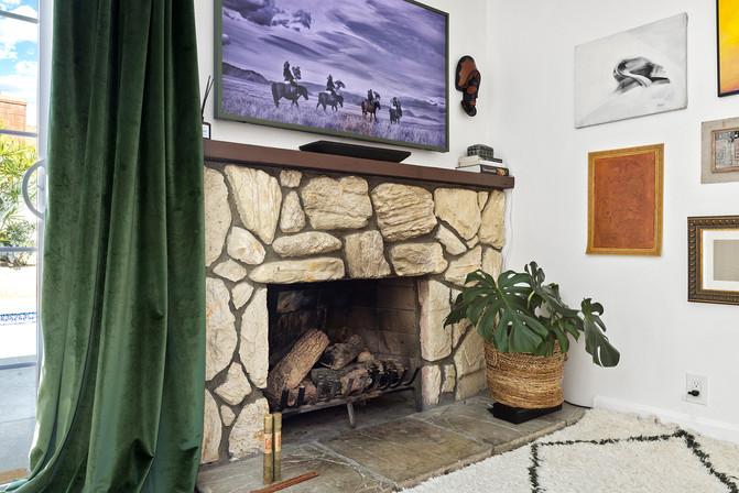 70s-stone-fireplace-green-velvet-drapes-moroccan-rug.jpg