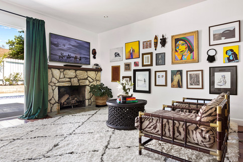 Living-room-green-velvet-drapes-african-coffee-table-bamboo-chairs-colorful-gallery-wall-art.jpg