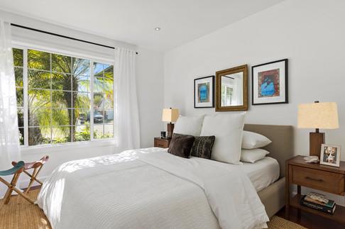 airy-guest-bedroom-linen-upholstered-bed-rattan-nightstands.jpg