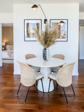 marble-pedestal-dining-table-cane-dining-chair-upholstered-seat-african-kuba-cloth-framed-wall-art-dining-room.jpg