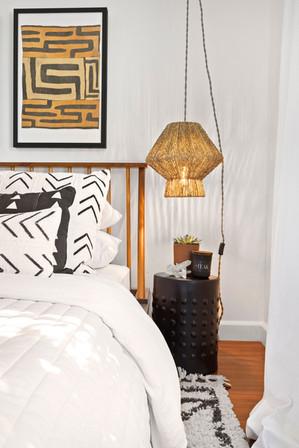 guest-bedroom-black-ceramic-nightstands-hanging-lights-framed-Kuba-cloth-wall-art.jpg