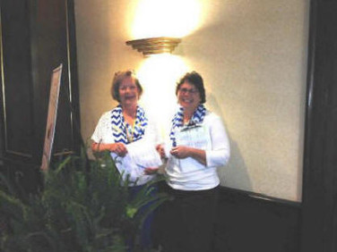 """Chapter Z's wonderful Steering Committee, Becky Hamilton (right)and Karen Love, did a fabulous job to help make Convention 2015 a success! Here they are """"conferencing"""" as they try to """"hide"""" behind the ferns."""