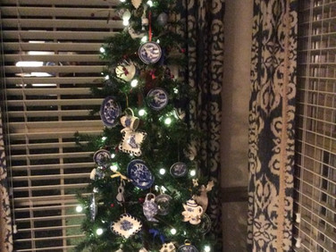 Small tree decorated in miniature china tea sets in blue and white patterns common in Britain.