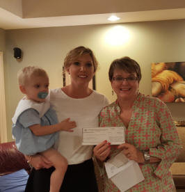 Janice Charlesworth is presenting a PCE check to Kylie McBrayer. She is holding her son Trip. Kylie is a teacher at Jeff Davis High School.