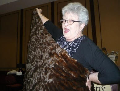 Auctioneer Janice Clifford getting sassy with fur throw auction item.