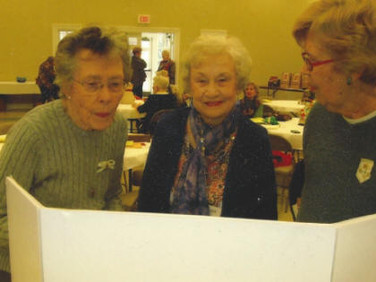 Peggy Schlemmer and Nadean Hankins taking Ouida Clark on a trip down Memory Lane.
