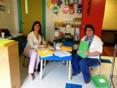 Suzanne Dorsett (left)and Becky Hamilton are hard at work putting together the folders of printed material that go into the convention bags.