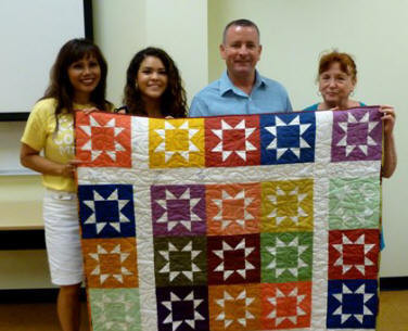 Gift quilt with the Rowell family, L to R, mother Linda, Tiara,  father Bill and grandmother Sharon