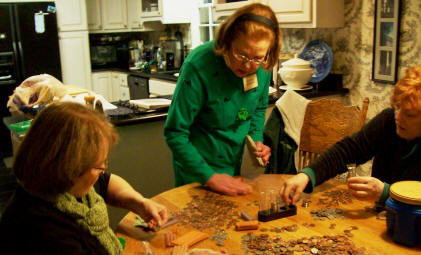 Mary Lou Rose, Marilyn Mooneyham, and Barb Mouton are counting the coins they saved.