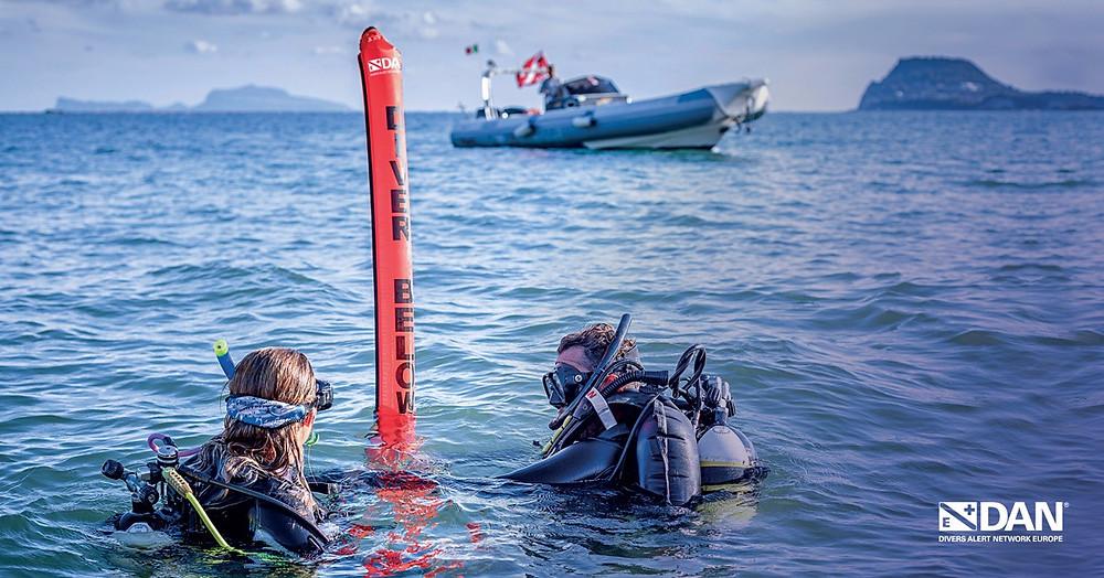 mergulhadores na superfície com decomark e barco DAN ao fundo
