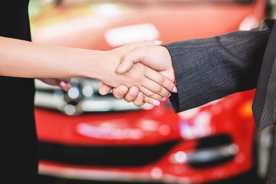 New Car vs Used Car Shaking Hands In Front Of Car, new car vs used car, advantages of new car, advantages of used car, disadvantages of used car, disadvantages of new car, should i buy old or new car, should i buy new or used car