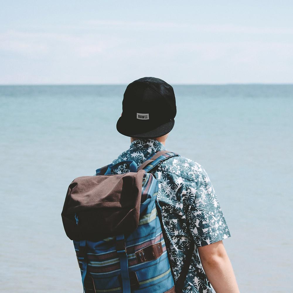 Mann mit Kappe am Strand