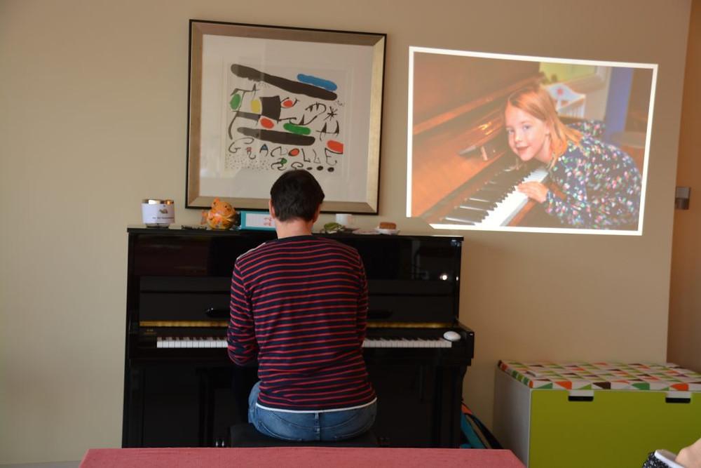 Bert aan de piano met naast hem, op de muur, een projectie van Aza, ook gezeten aan een piano.