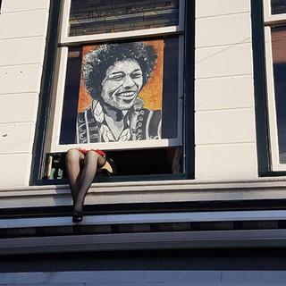 Jimi Hendrix in het raamkozijn met sexy legs eronder, grapje
