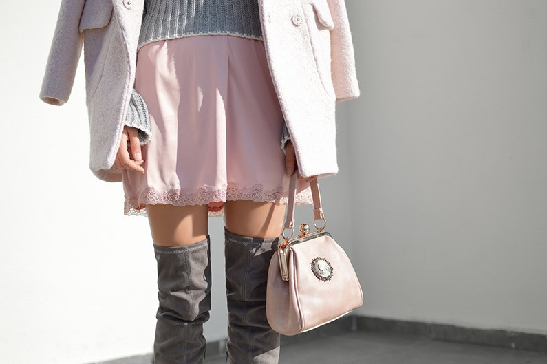 Woman in pink outfit and grey over-the-knee boots