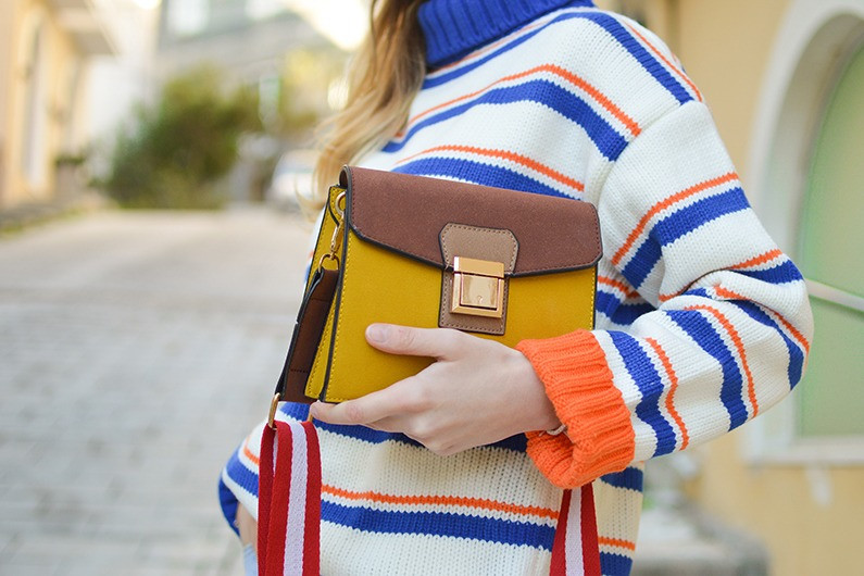 Women in striped knit with handbag