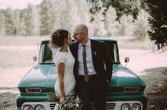 Photo of wedding couple sitting on a car