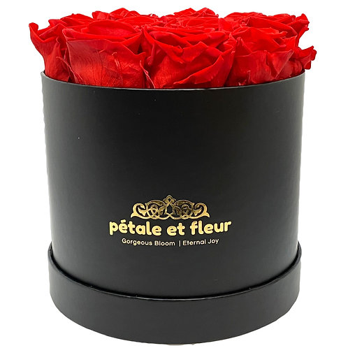 Twelve red roses in a round black box