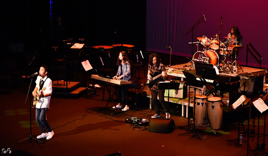 rock band performance with guitar, piano, congo, drums and vocals at a concert