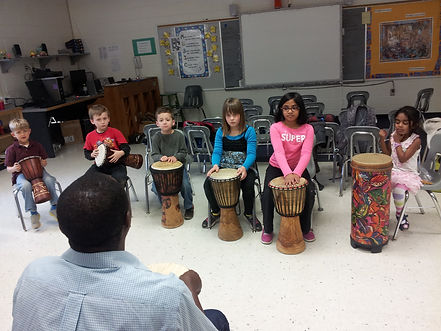 percussion ensemble with djembe, drums, percussion instruments with children in muisc class
