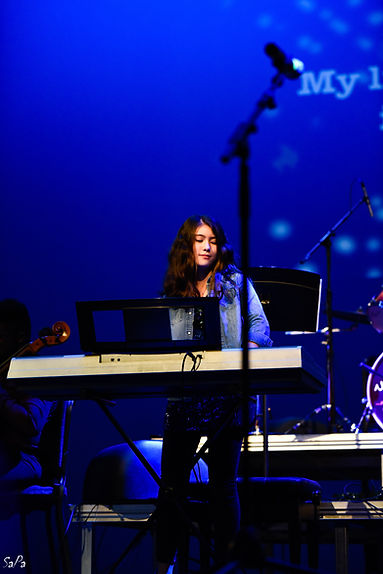 student performing piano in a concert event at hylton performing arts center