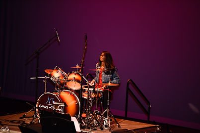 girl playing drums to a rock song in hylton performing art center manassas virginia