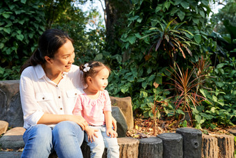 Mother-and-daughter-resting-on-stump