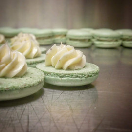 Pistachio Macaroons being filled with Cream.