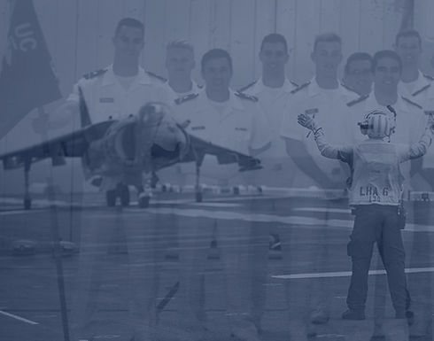 Midshipmen in summer white uniforms serve as a background to an image of a carrier deck.