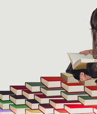 Girl reading a book sitting on a tower of books
