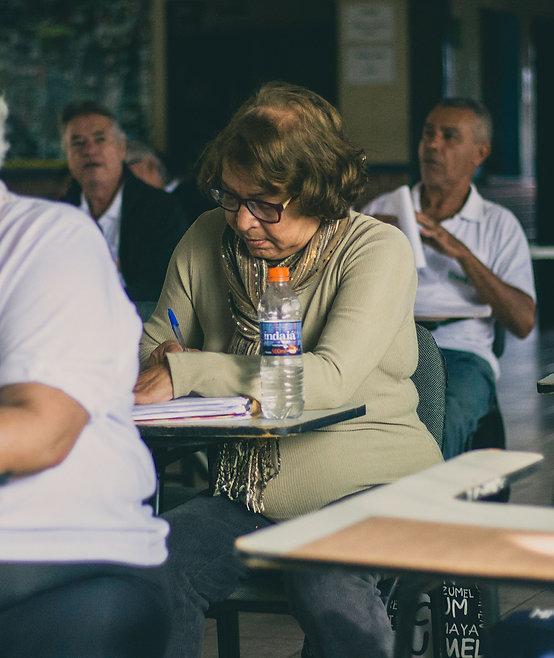 Aluna da UniSER com uma caneta e caderno na mão fazendo anotação durante uma aula.
