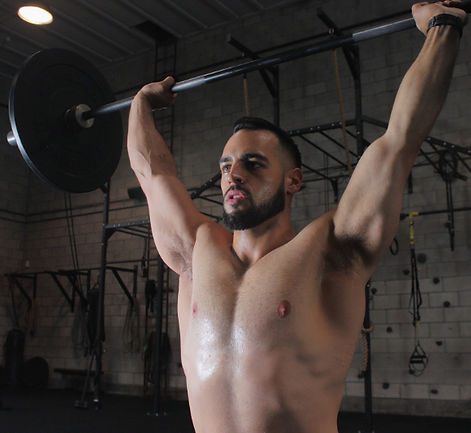 Overhead barbell press performed in a crossfit gym. This picture was taken in San Francisco