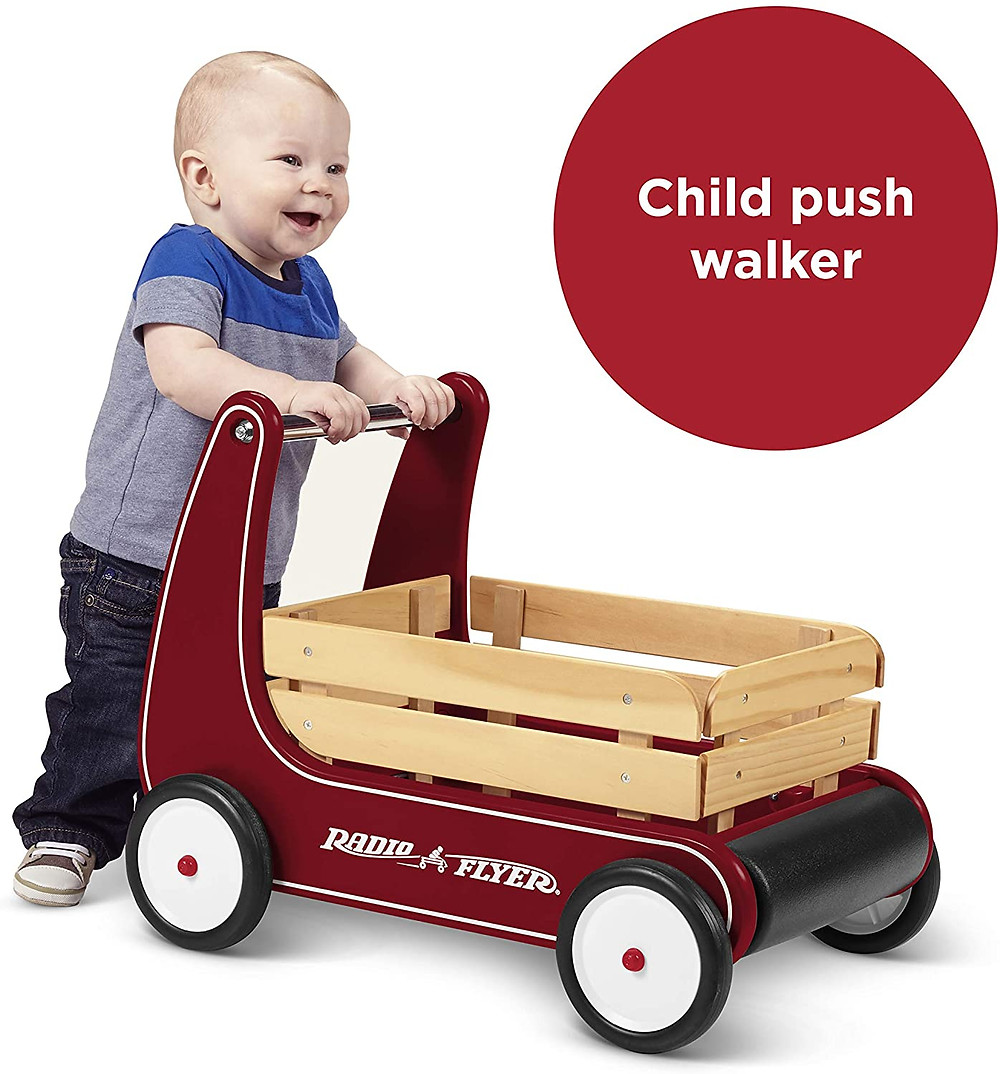 smiling toddler walking with radio flyer push walker