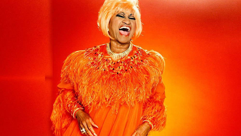 Celia cruz singing on stage orange background