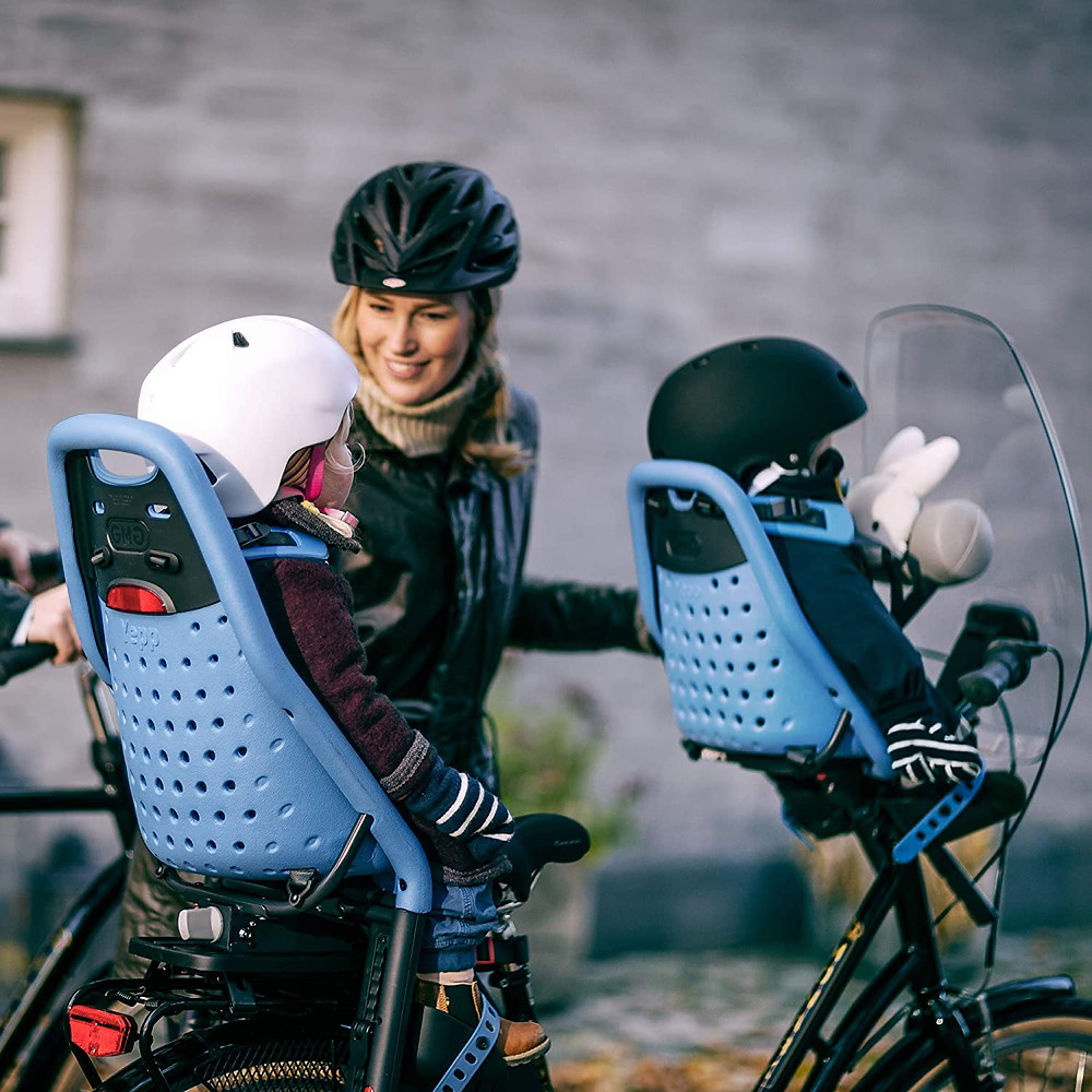 Mother smiling at child as she buckles children into bicycle seats wearing helmets