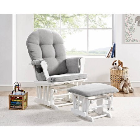 Baby nursery with gray rocking chair and foot stool and baby items around