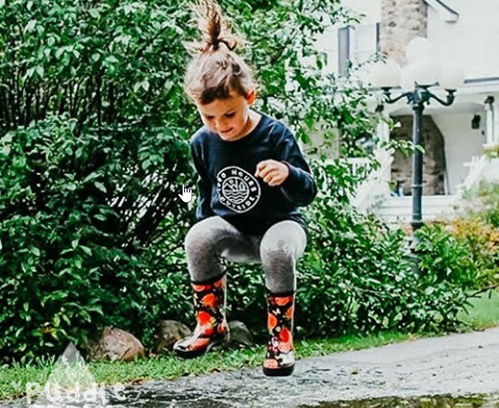 Little girl wearing rainboots jumping in puddle