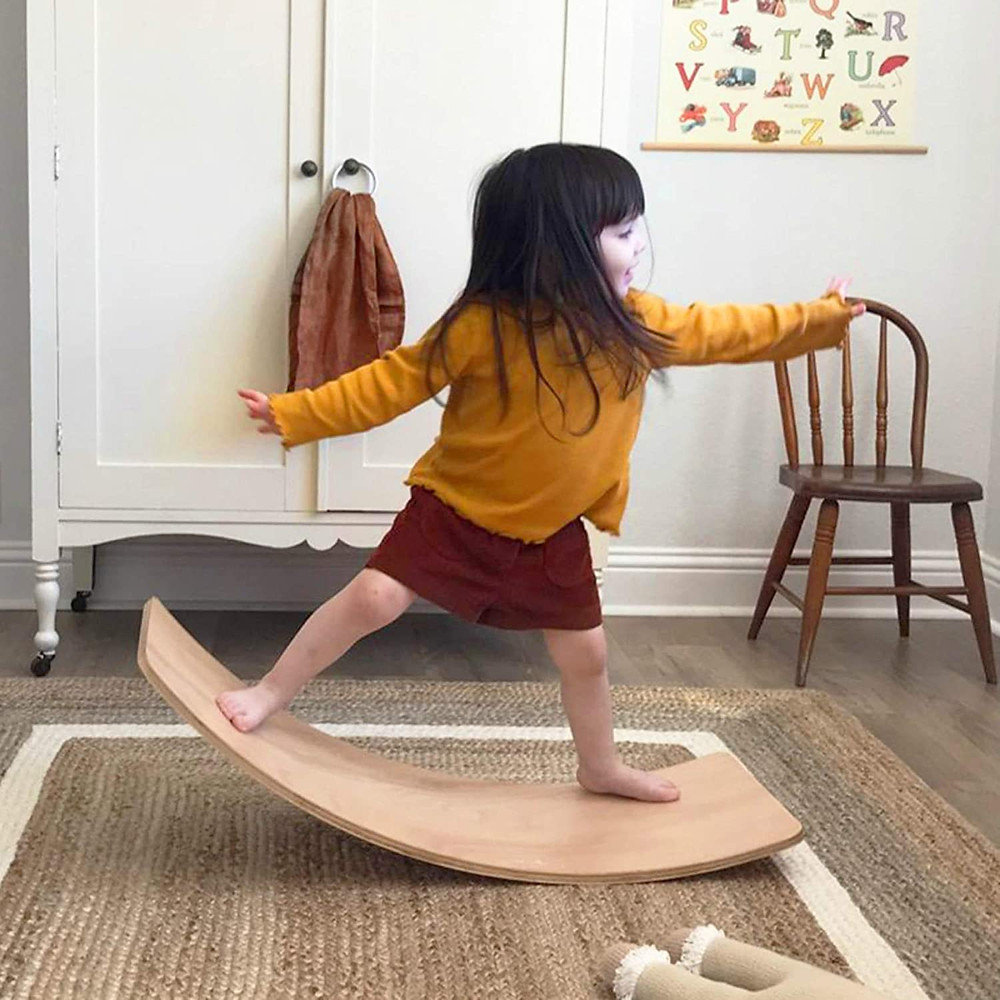 Little girl standing on curvy board in livingroom