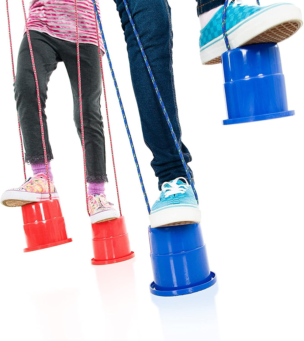 legs and feet of kids playing with red and blue EZ stepper stilts