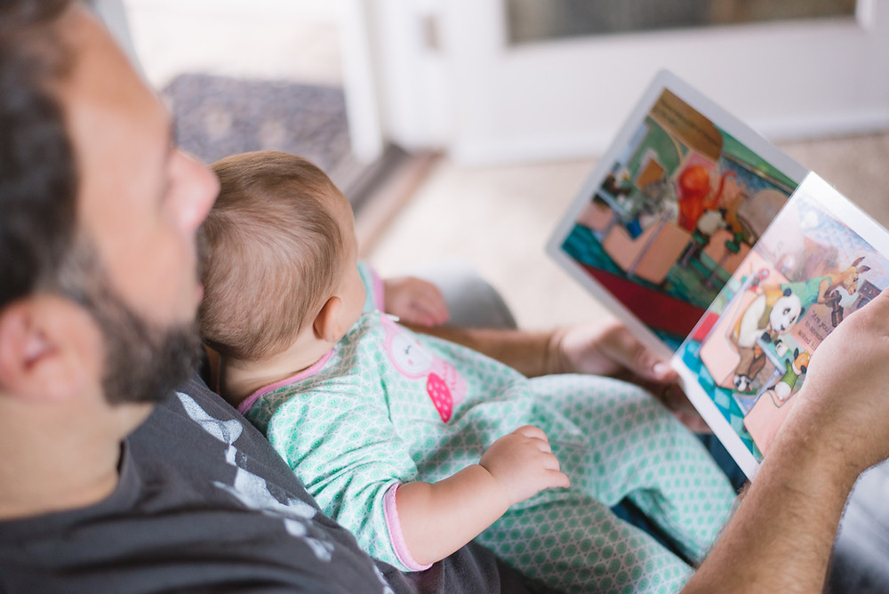 father reading a book to baby bilingual